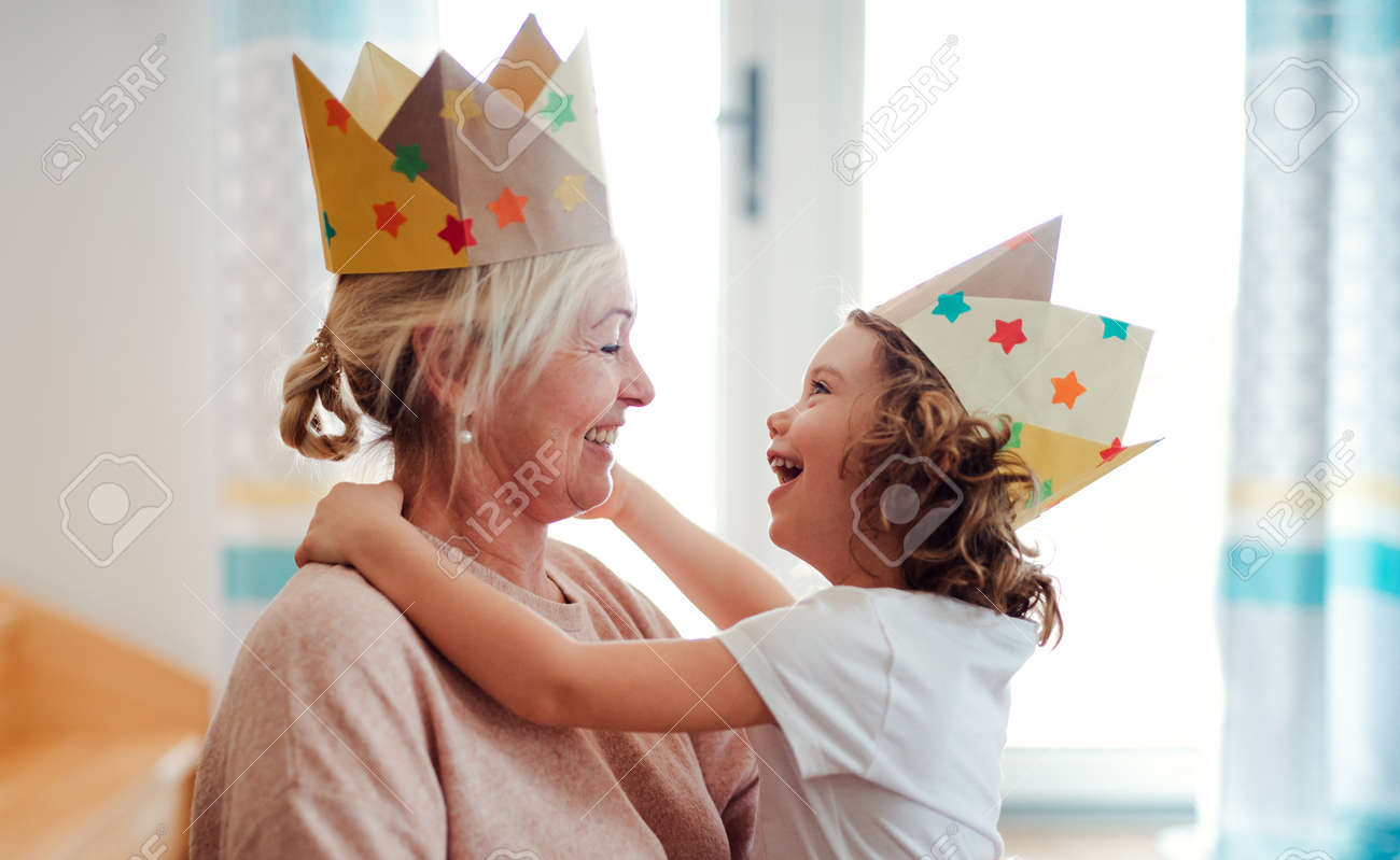 A portrait of small girl with grandmother having fun at home. - 119145799