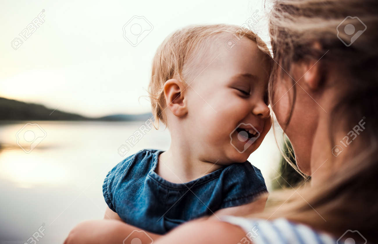 A close-up of mother with a toddler daughter outdoors by the river in summer. - 121219449