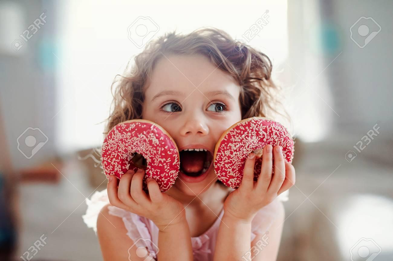 A small girl with doughnuts at home, looking at camera. - 121281941