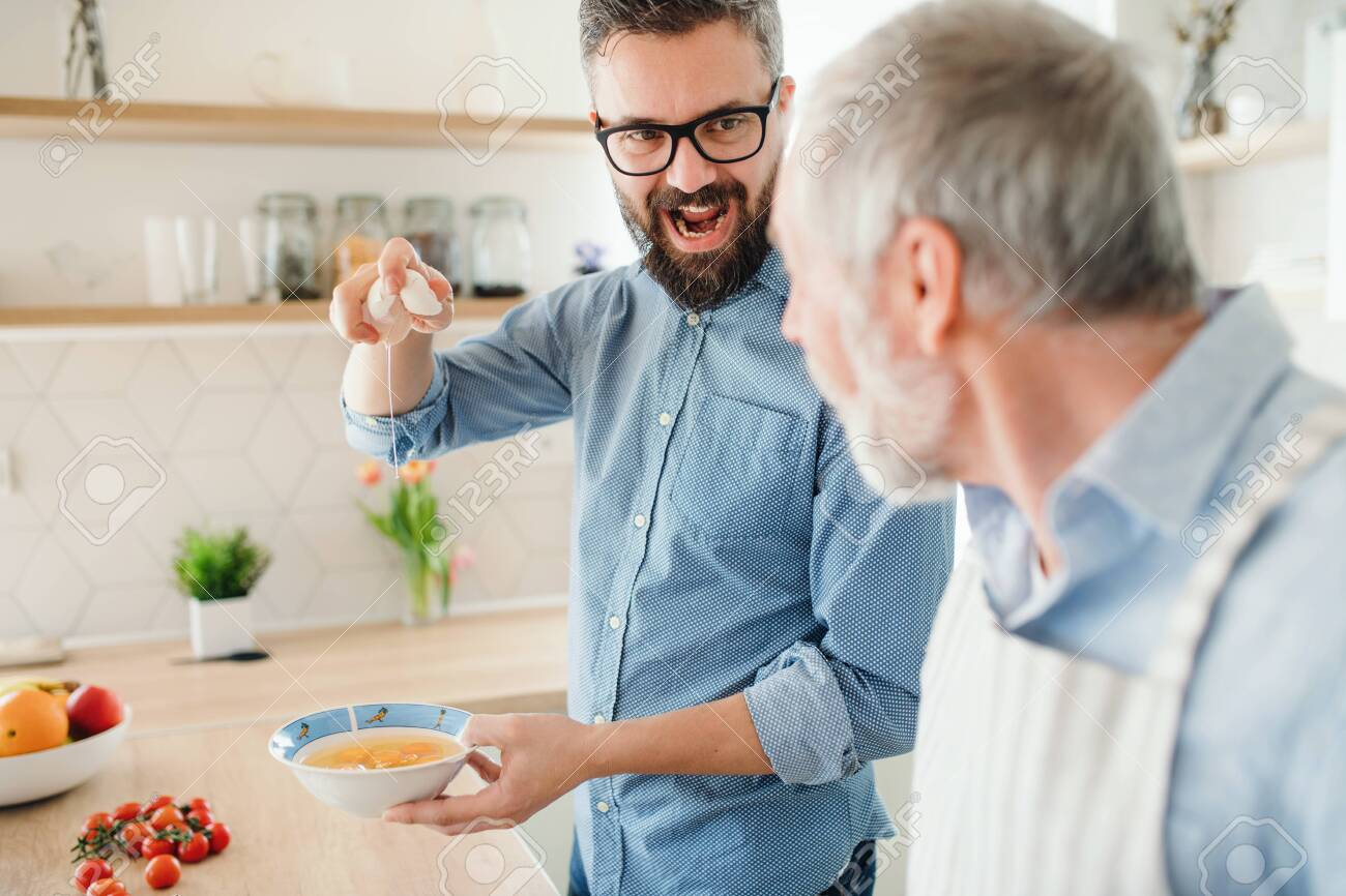 An adult hipster son and senior father indoors at home, cooking. - 122964267