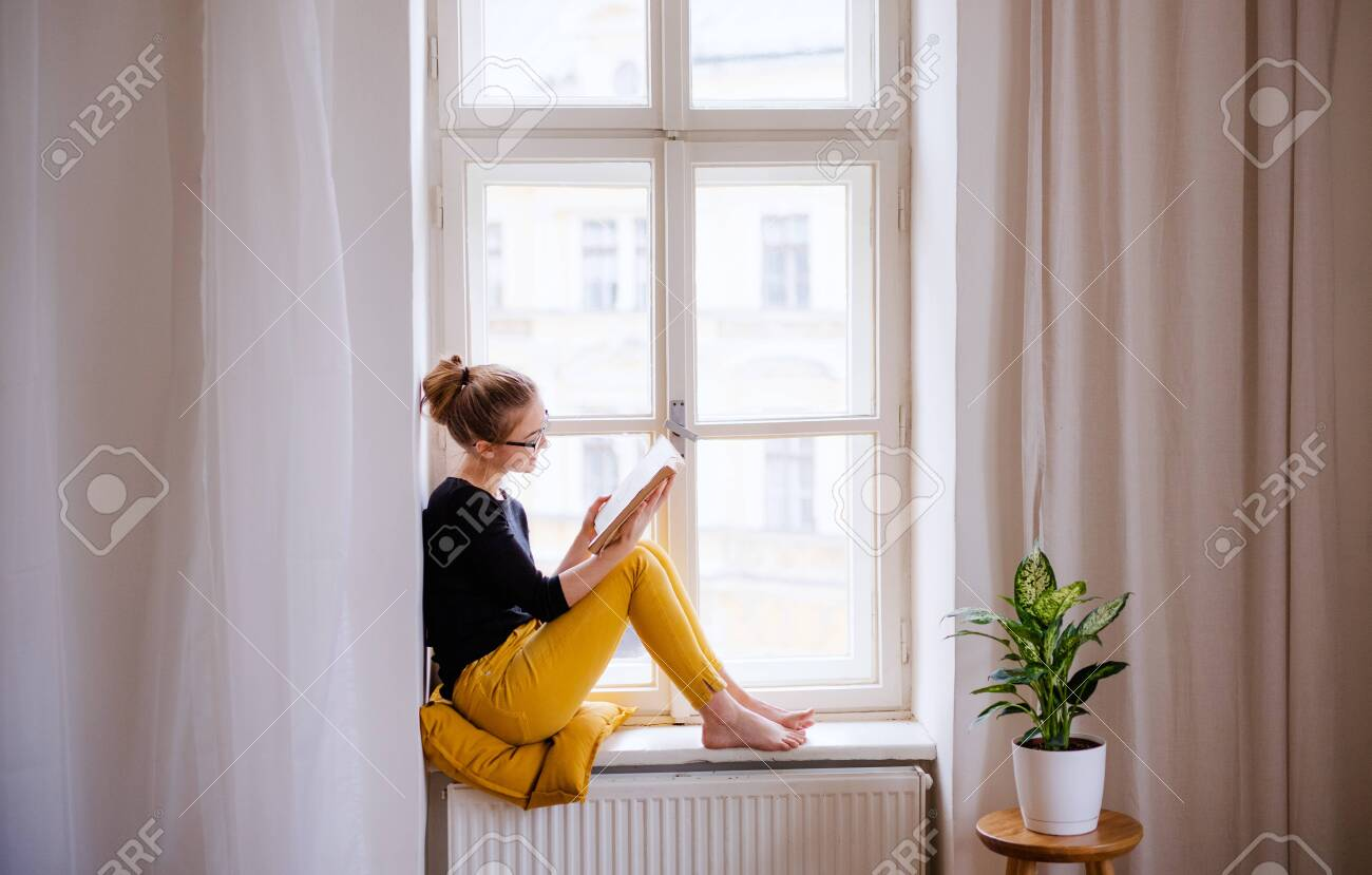A young female student with a book sitting on window sill, studying. - 124677791