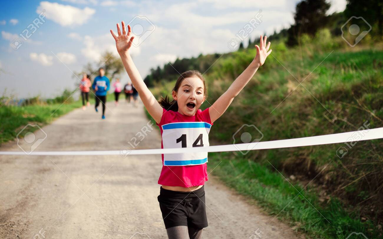 Small girl runner crossing finish line in a race competition in nature. - 124975837