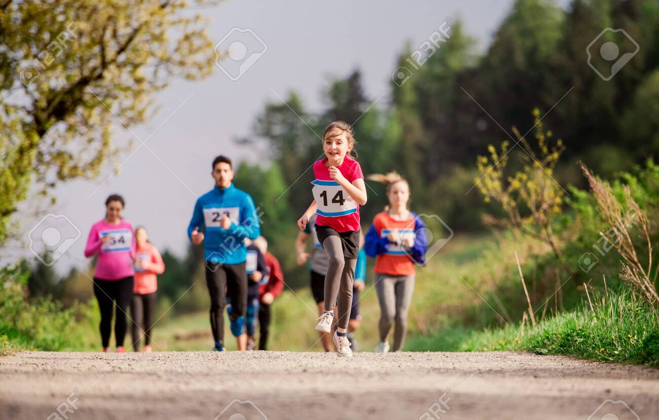 Large group of multi generation people running a race competition in nature. - 125559306
