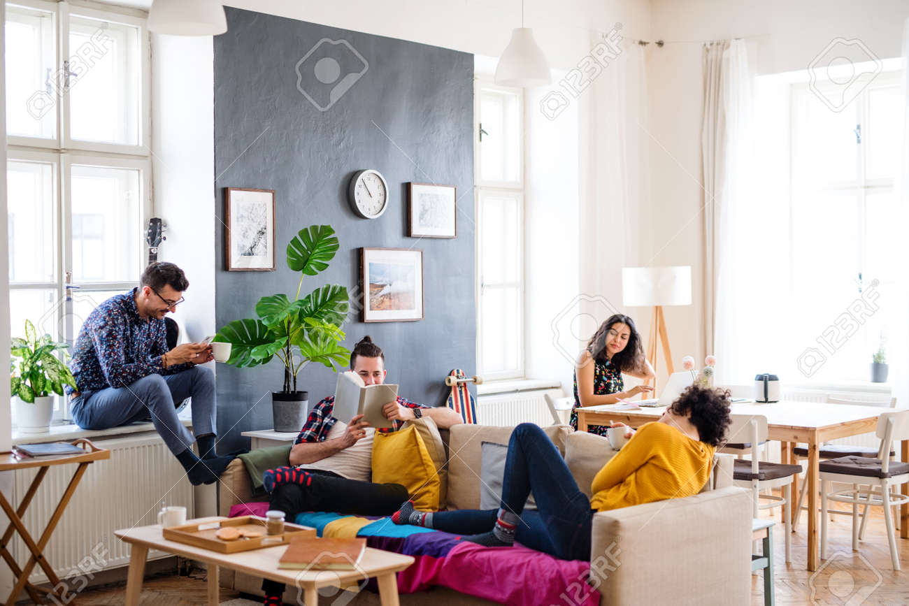 A group of young friends relaxing indoors, house sharing concept. - 128238978