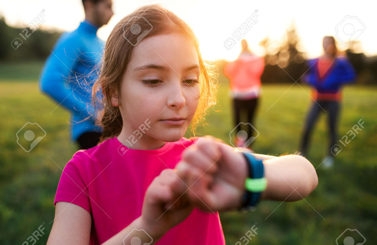 A portrait of small girl with large group of people doing exercise in nature. - 128662501