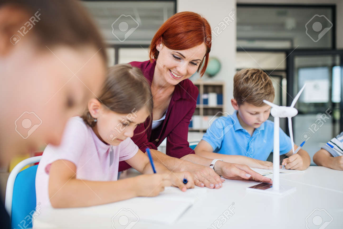 A group of small school kids with teacher in class learning about environment. - 129017447