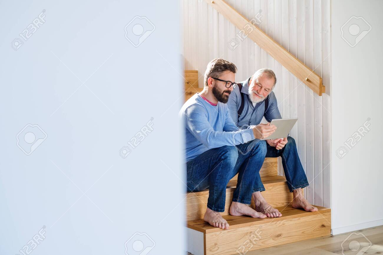 An adult son and senior father with tablet sitting on stairs indoors at home. - 129679555
