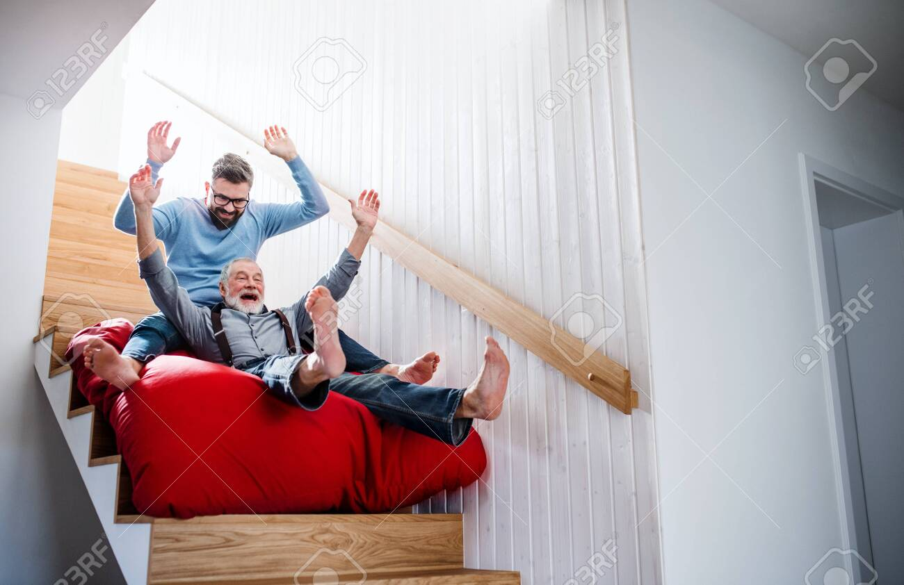 An adult hipster son and senior father indoors at home, having fun. - 131323460