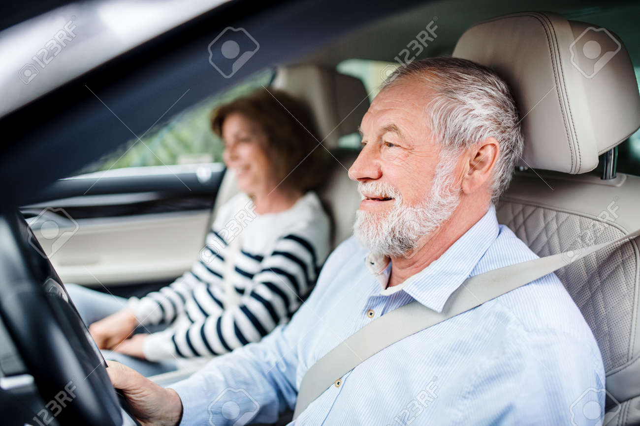 Happy senior couple with smartphone sitting in car, driving,. - 131323269
