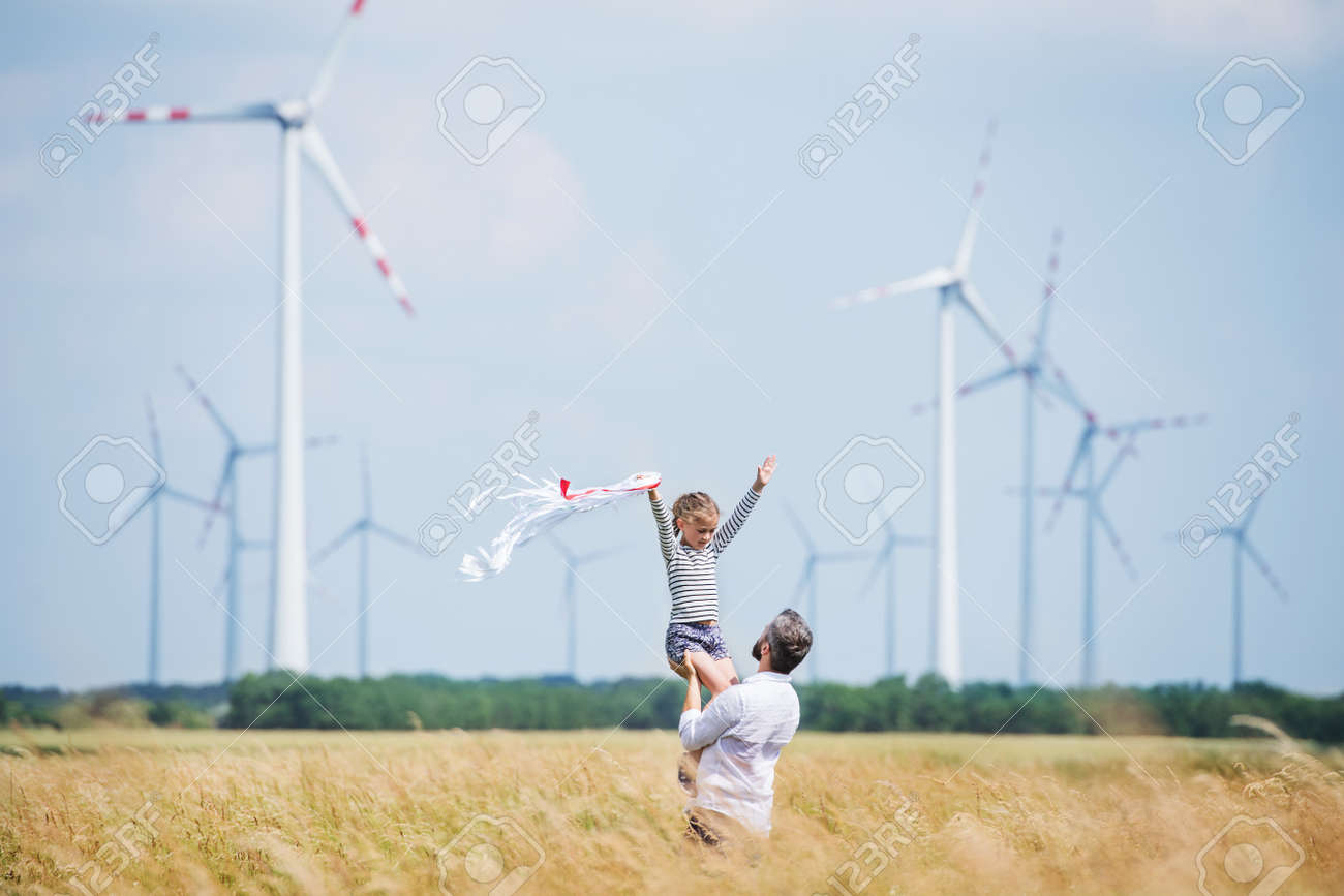 Mature father with small daughter standing on field on wind farm. - 132303803