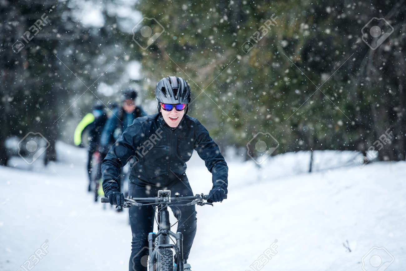 Group of mountain bikers riding on road outdoors in winter. - 133254327