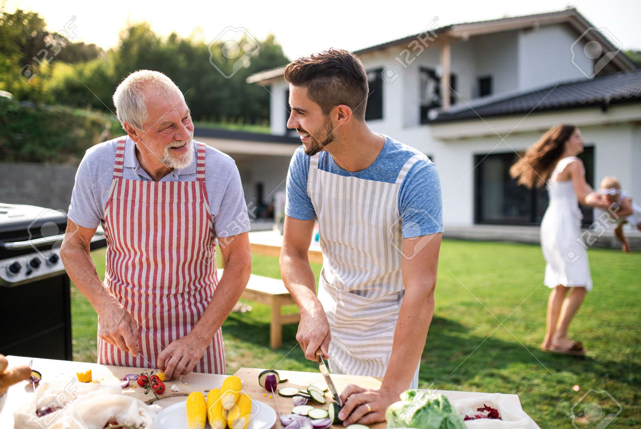 Portrait of father and son outdoors on garden barbecue, grilling. - 133937727