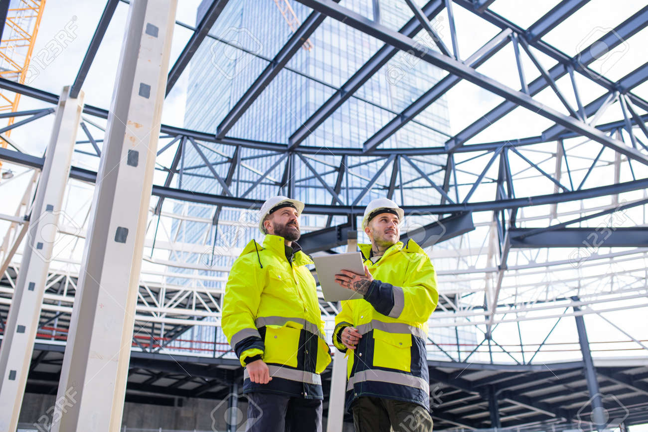 Men engineers standing outdoors on construction site, using tablet. - 139930301