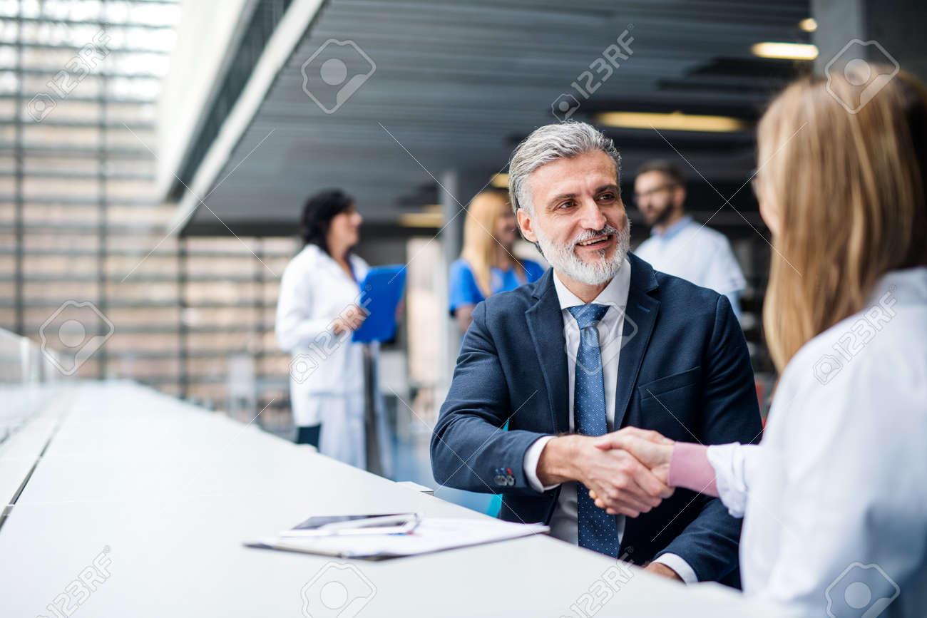 Doctors talking to pharmaceutical sales representative, shaking hands. - 142682932