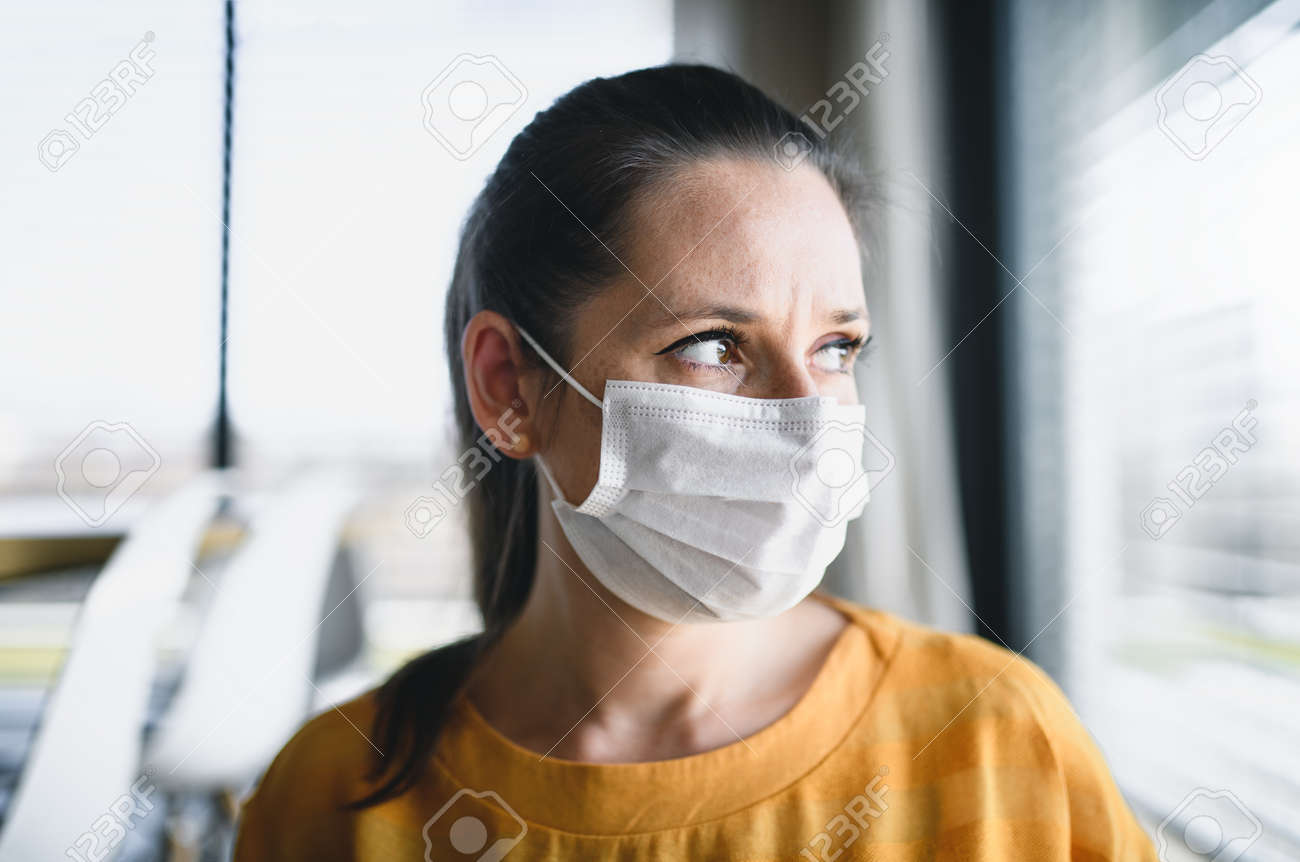 Woman with face masks indoors at home, Corona virus and quarantine concept. - 143699492