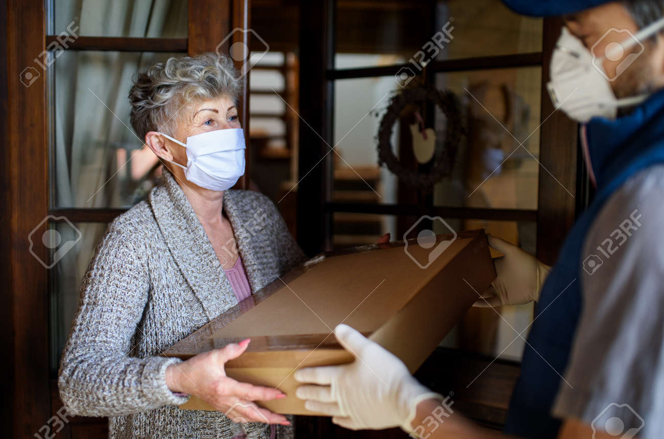 Courier with face mask delivering parcel to senior woman, corona virus and quarantine concept. - 144461058