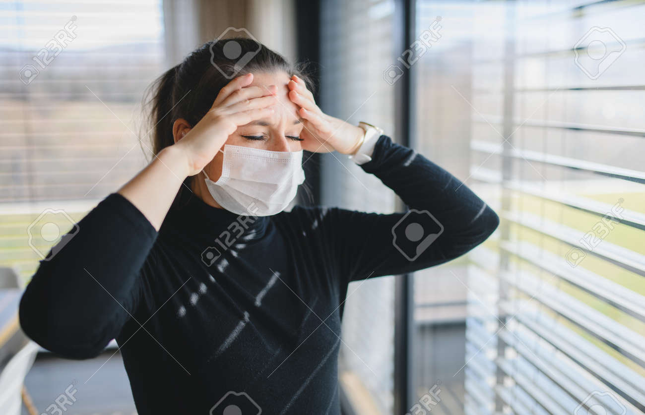 Woman with headache and face masks indoors at home, Corona virus concept. - 144720744