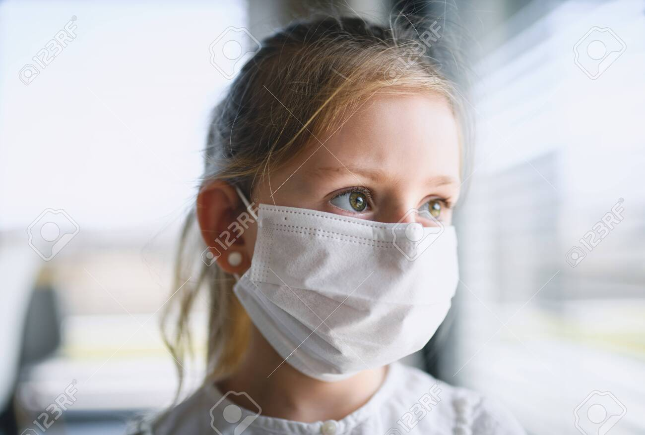 Small girl with face masks indoors at home, Corona virus and quarantine concept. - 144720751