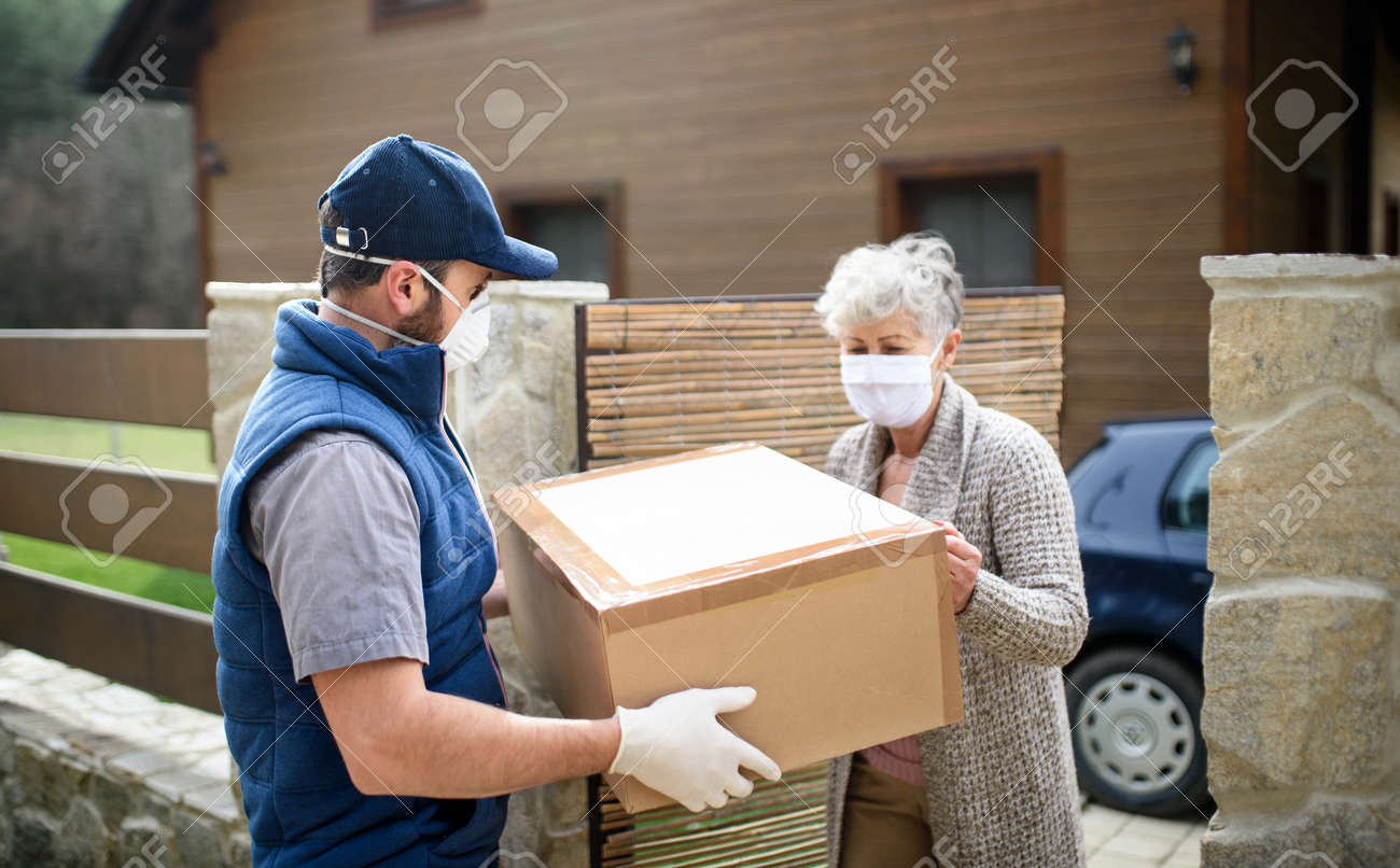 Courier delivering parcel to senior woman with face mask, corona virus and quarantine concept. - 144720764