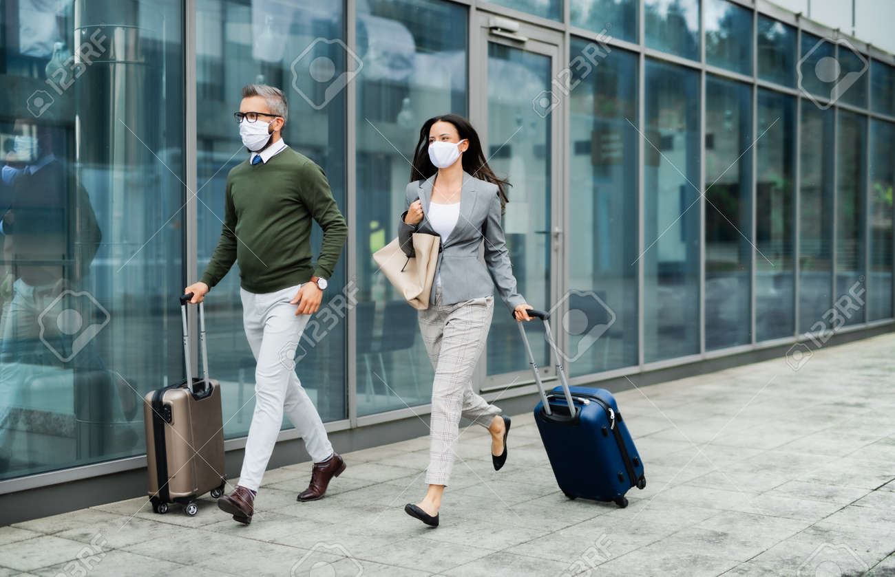 Businesspeople with luggage going on business trip, wearing face masks at the airport. - 149437626