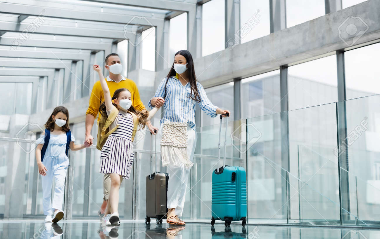Family with two children going on holiday, wearing face masks at the airport. - 149439387
