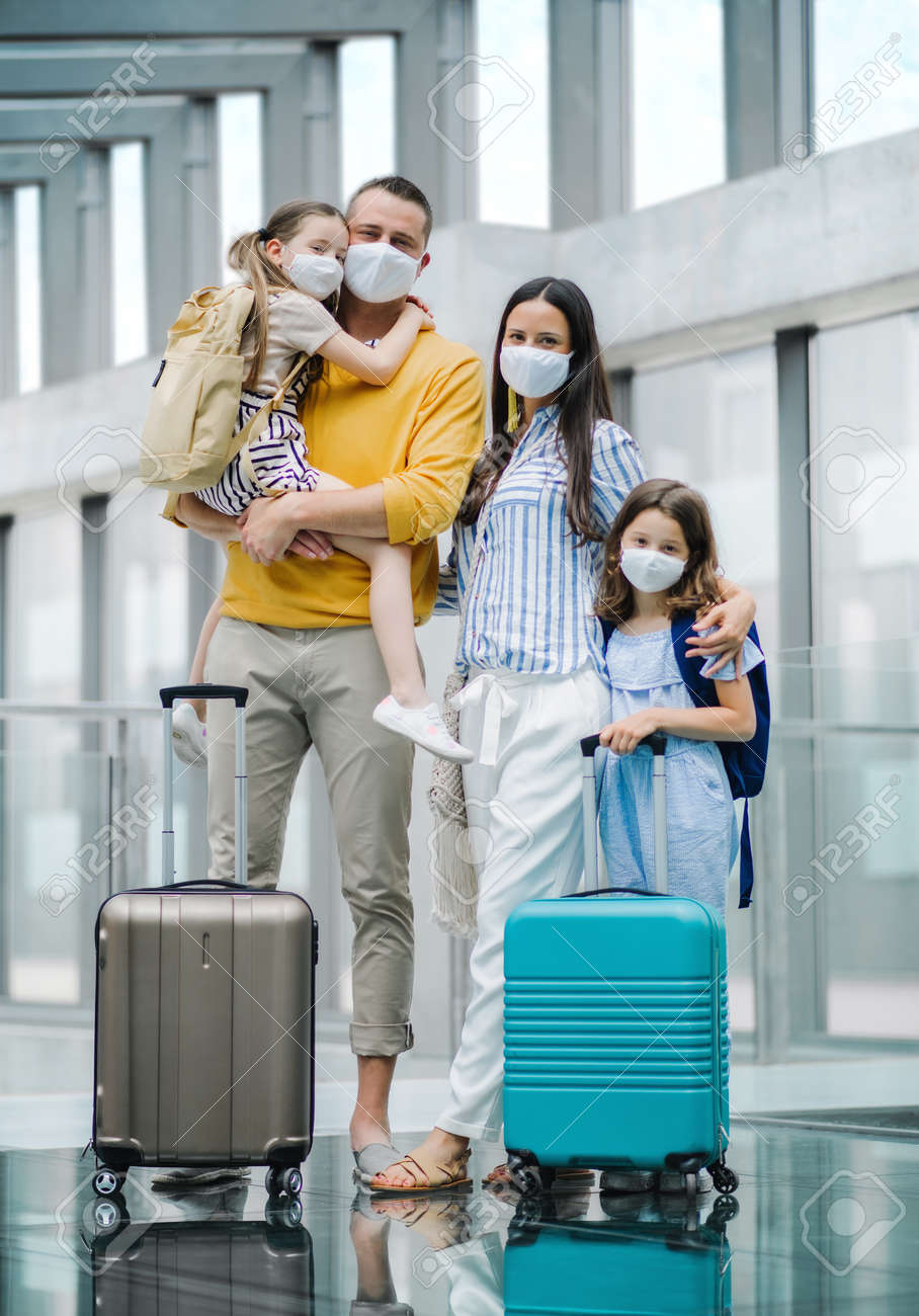 Family with two children going on holiday, wearing face masks at the airport. - 149899425