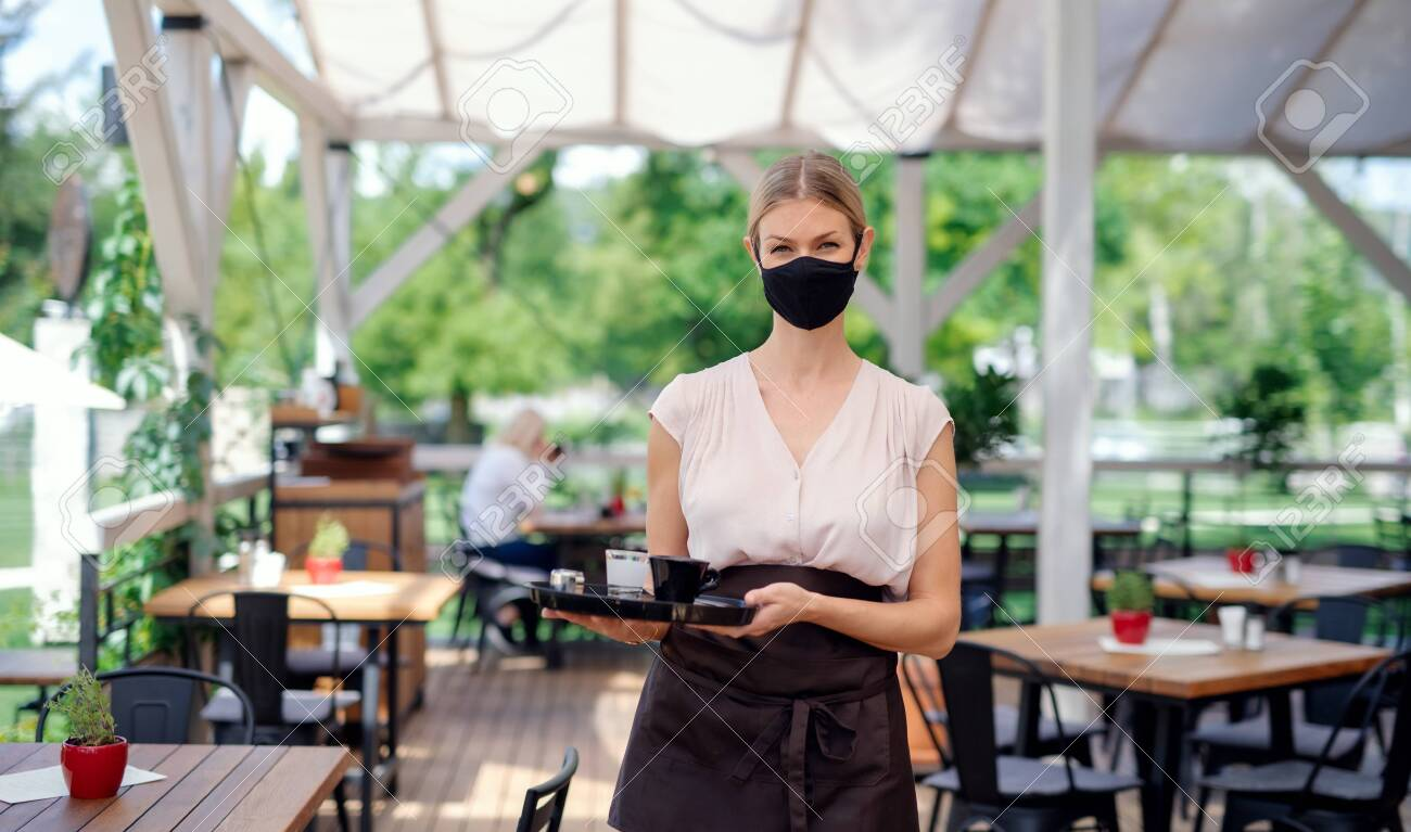 Waitress with face mask serving customers outdoors on terrace restaurant. - 150432340