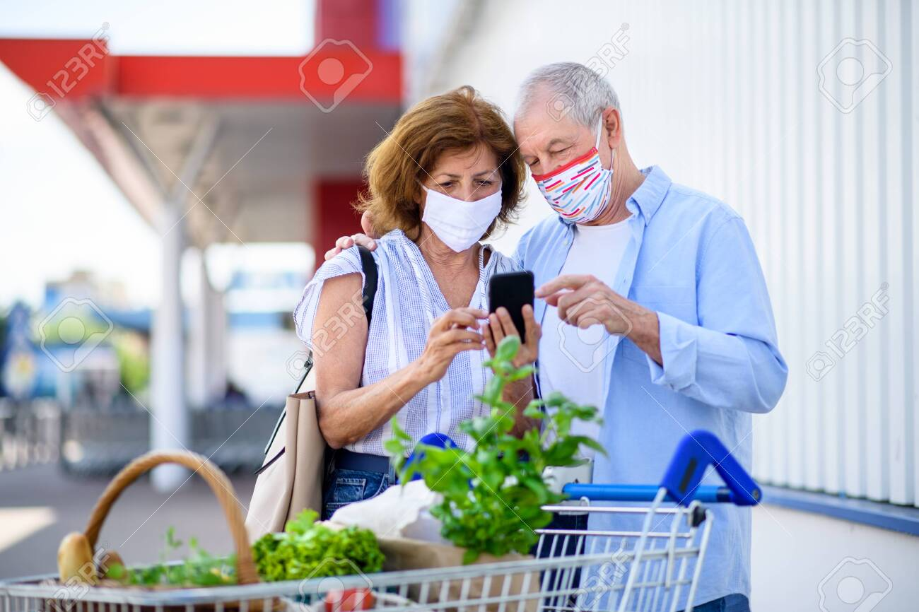 Senior couple with face masks and shopping with smartphone outside supermarket in city. - 152468227