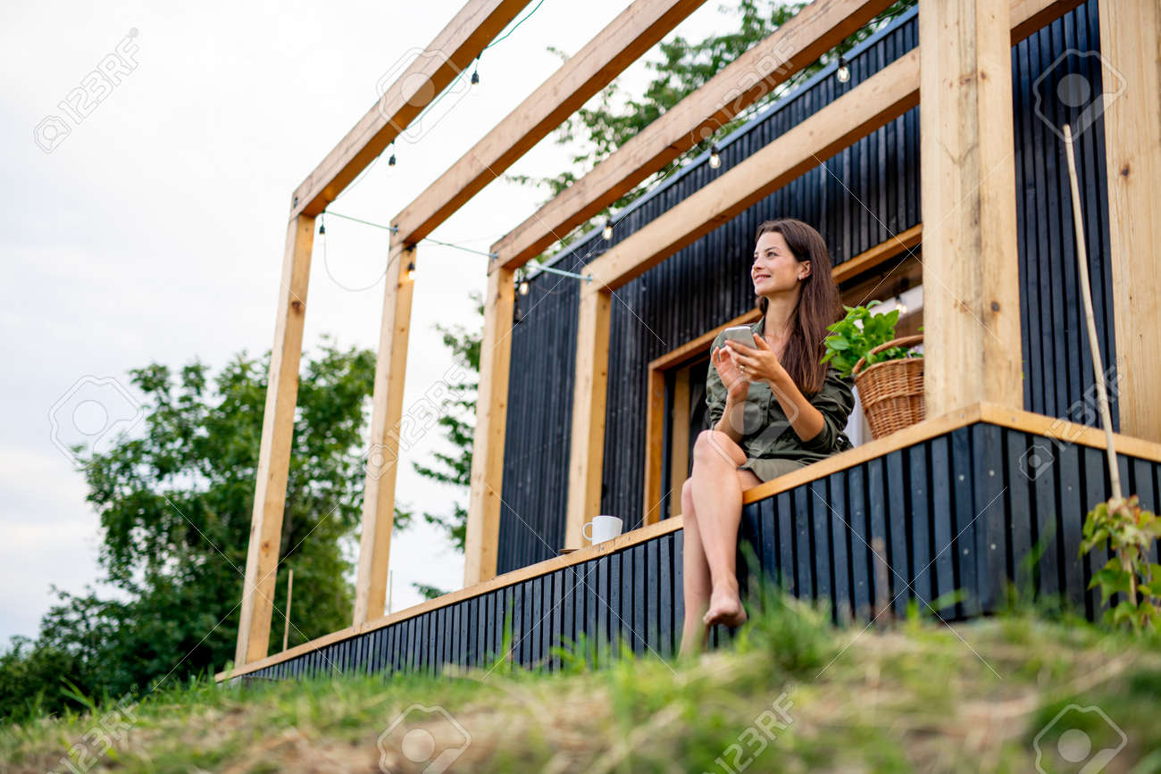 Young woman with smartphone outdoors, weekend away in container house in countryside. - 154673693