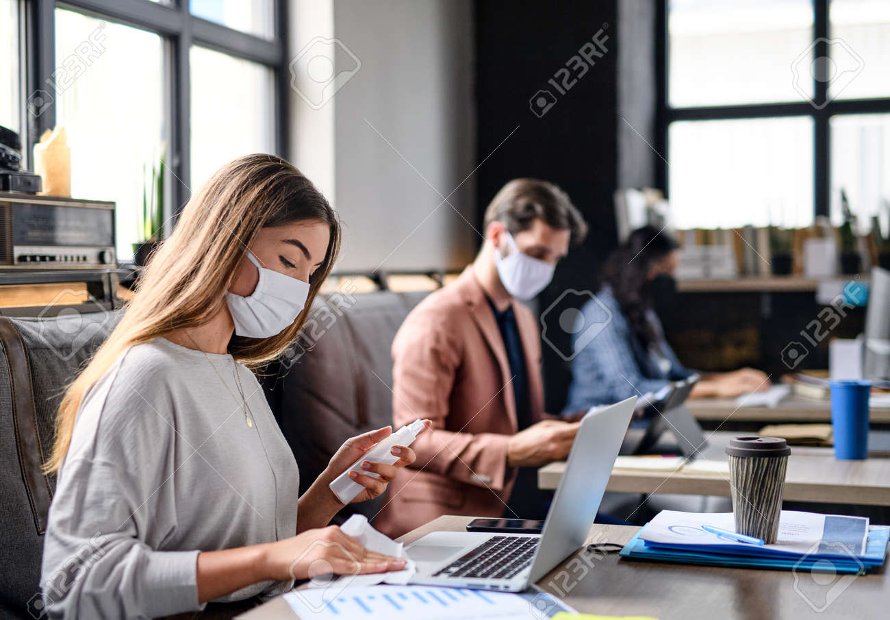 Portrait of young businesspeople with face masks working indoors in office, disinfecting laptop. - 155417596