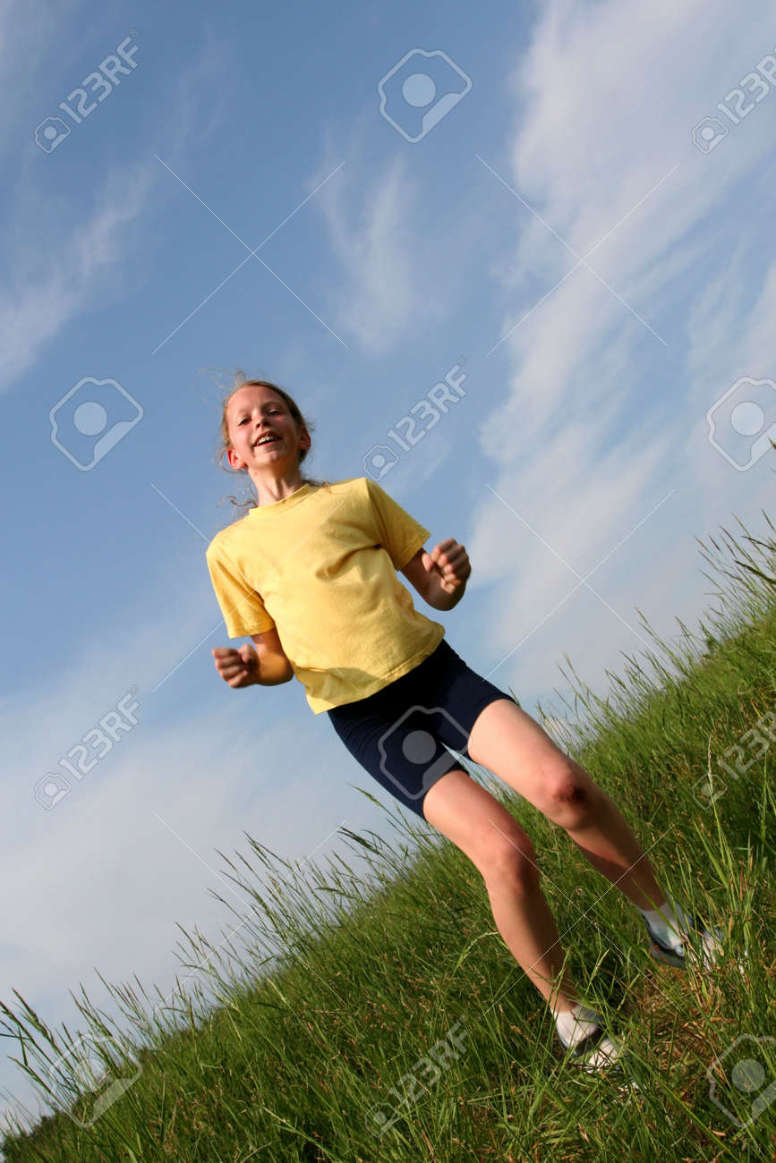 Young girl jumping in grass on a blue sky background. Motion blur Stock Photo - 1067779