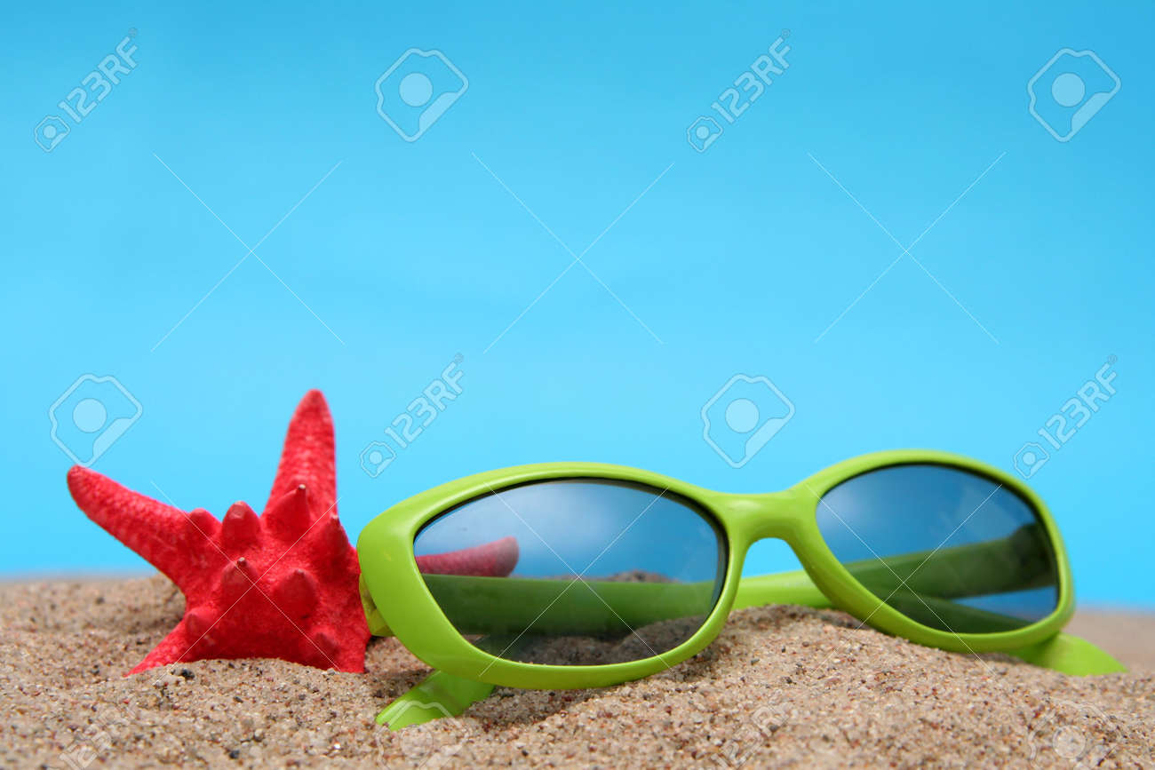 Green sunglasses and sand on a blue background Stock Photo - 1356537
