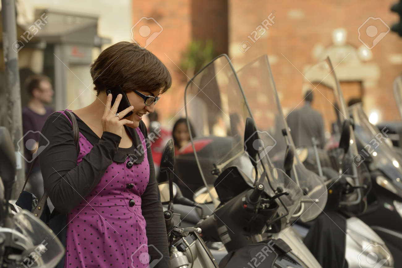 woman in San Babila  1, Milan, young woman makes her way among scooters parked in city center, in the same time is using a cellphone and smiles notwithstanding the chaos Stock Photo - 18068463
