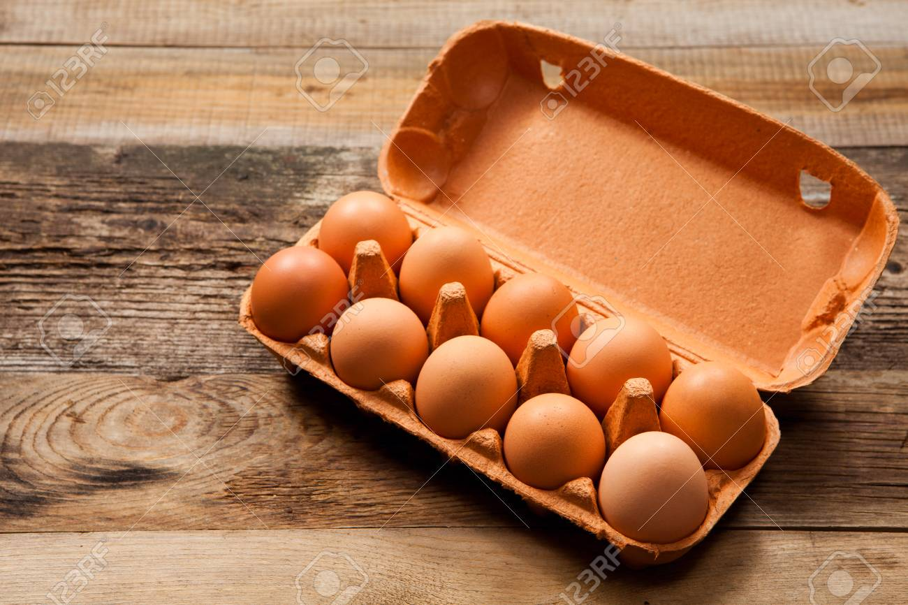 Eggs in the package on wooden table - 29489665