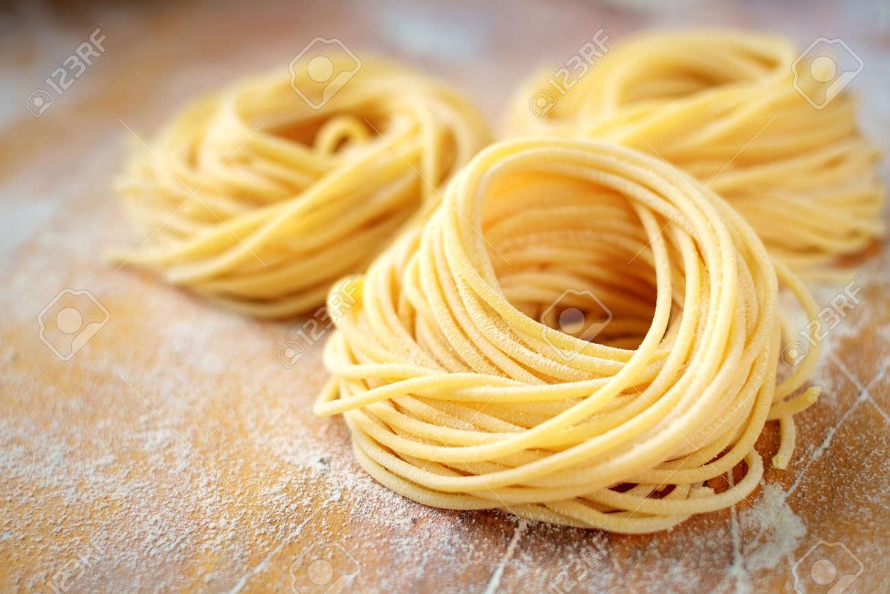 raw homemade spaghetti nest with flour on a wooden table. fresh Italian pasta - 123491329