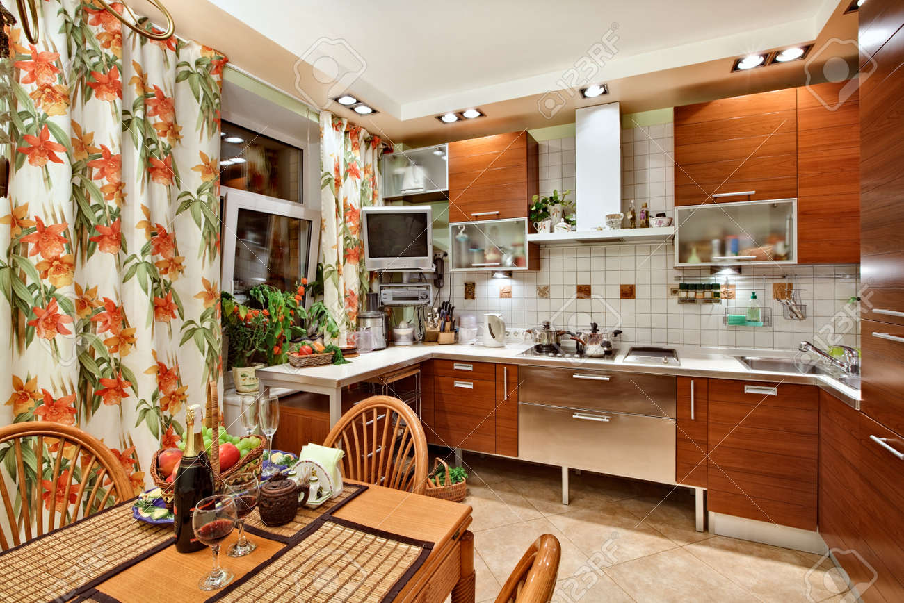 Kitchen interior with wooden furniture, table and many utensils in warm tones on wide angle view Stock Photo - 7478647