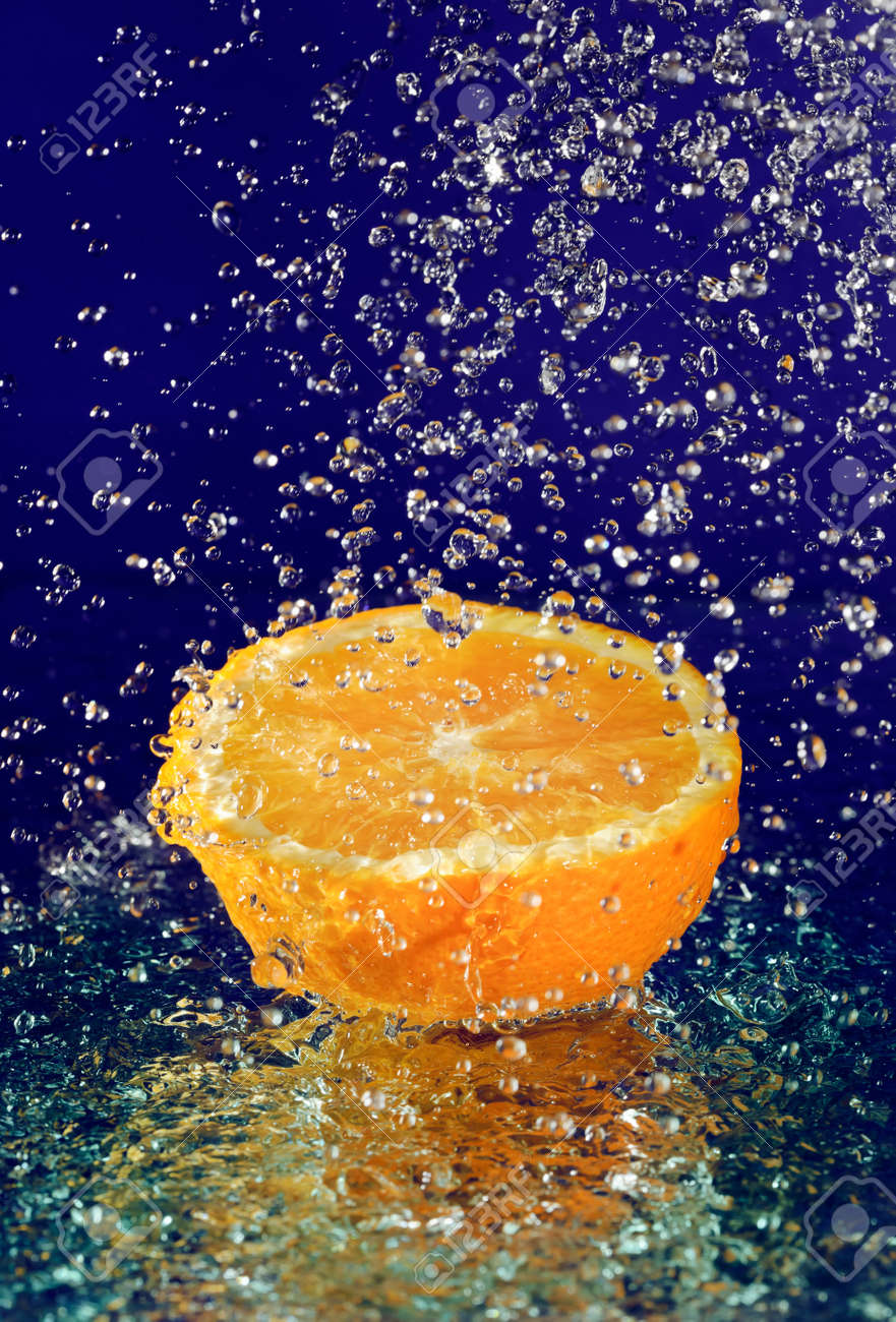 Half of orange with stopped motion water drops on deep blue Stock Photo - 8324708