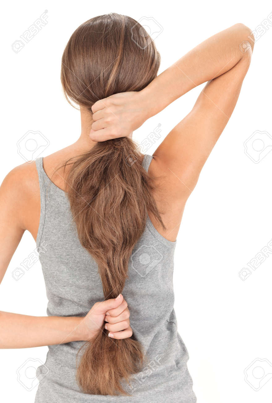 Brunette lady holding long hairs, view from back side isolated on white Stock Photo - 8771303