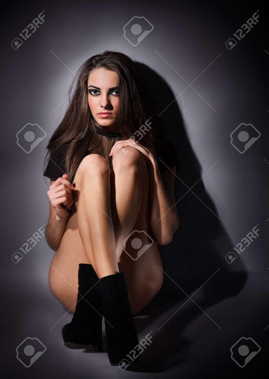 Young slim glamour lady with long hairs dressed in black combi dress sitting on the floor, dark key studio portrait Stock Photo - 9086542