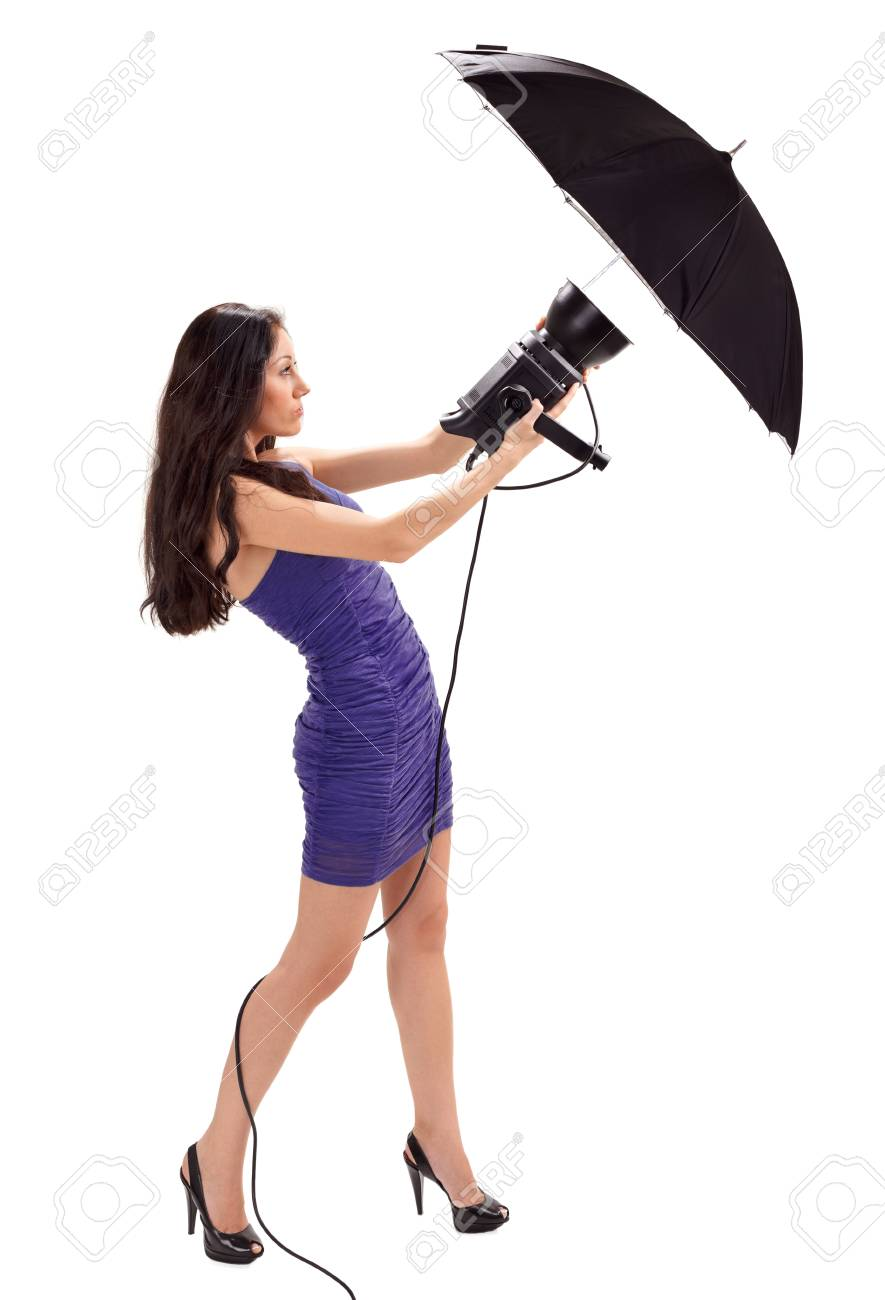 Young pretty lady in blue dress holding studio flash with umbrella isolated on white Stock Photo - 9086621