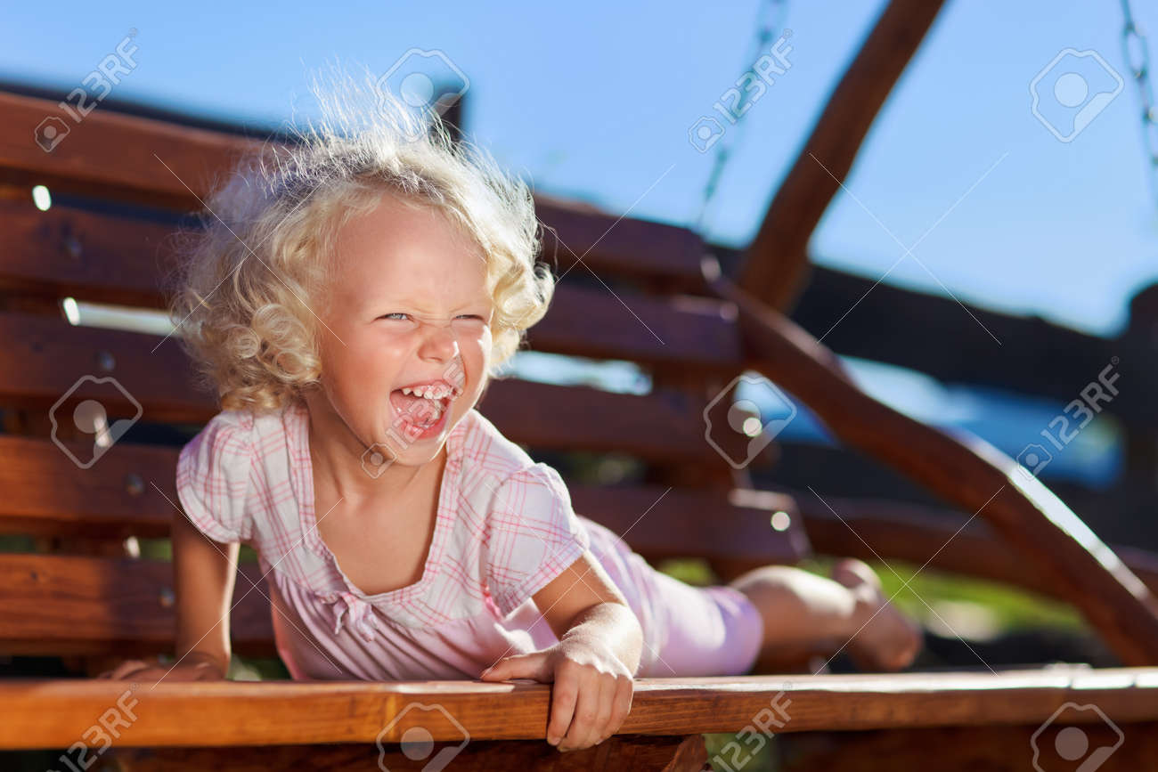 Cute little girl with blond curly hair playing on wooden chain swing Stock Photo - 9295777