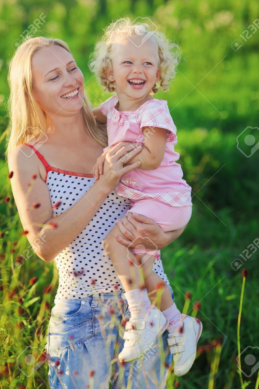 Beautiful mother with infant curly-headed blond daughter on meadow in sunset sun beams Stock Photo - 9783220