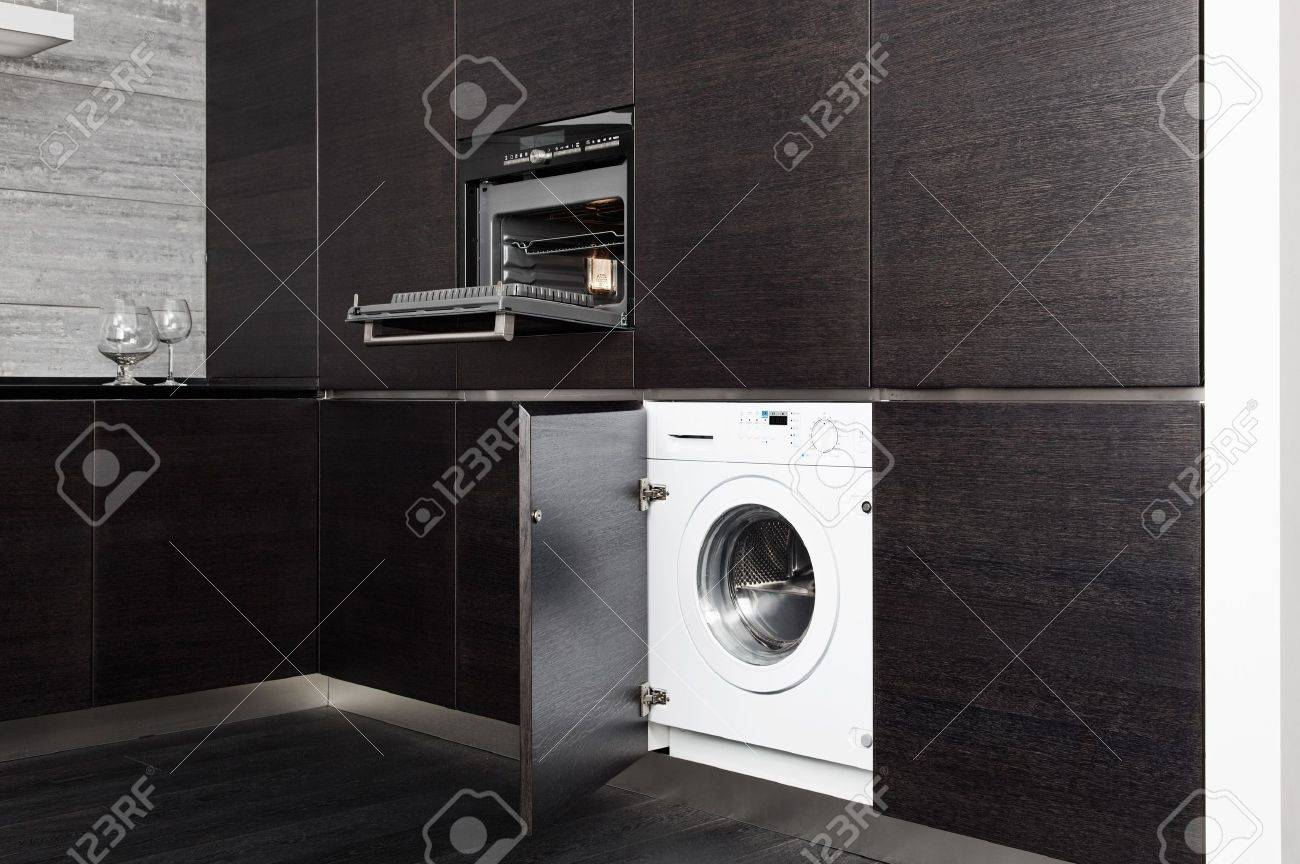 build-in washing machine and cooker on modern black kitchen