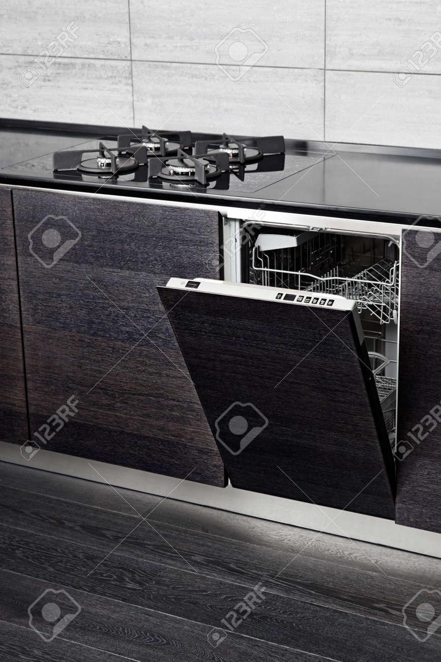 Open dish washer machine and gas-stove on black hardwood kitchen Stock Photo - 15766990