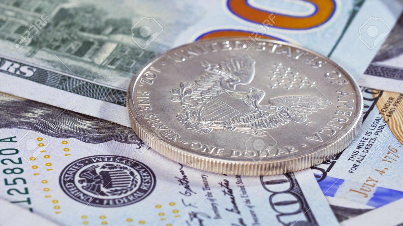 Ein Dollar Silber American Eagle Münze über Banknoten Hintergrund
