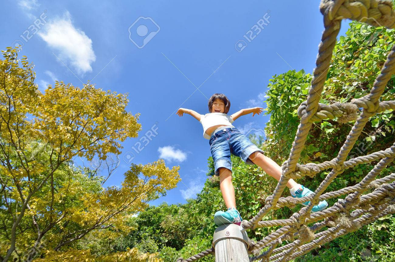 A girl playing at the playground in the Park - 54132409