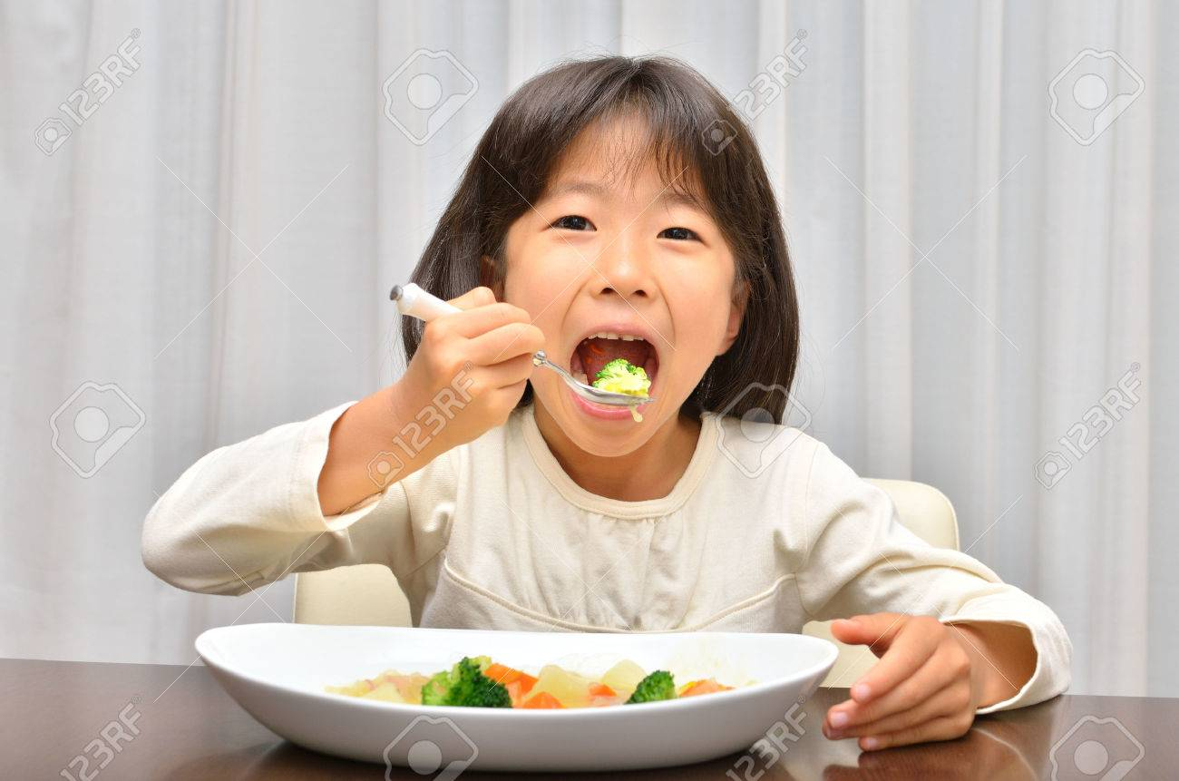 Girl eating delicious stew - 57094516