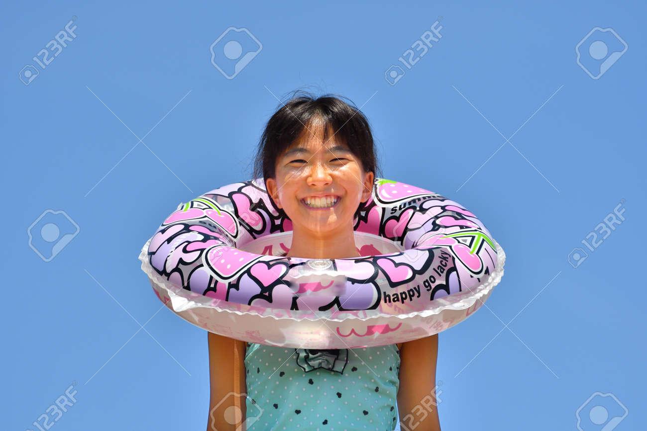Japanese girl enjoys sea bathing - blue sky - 130423238