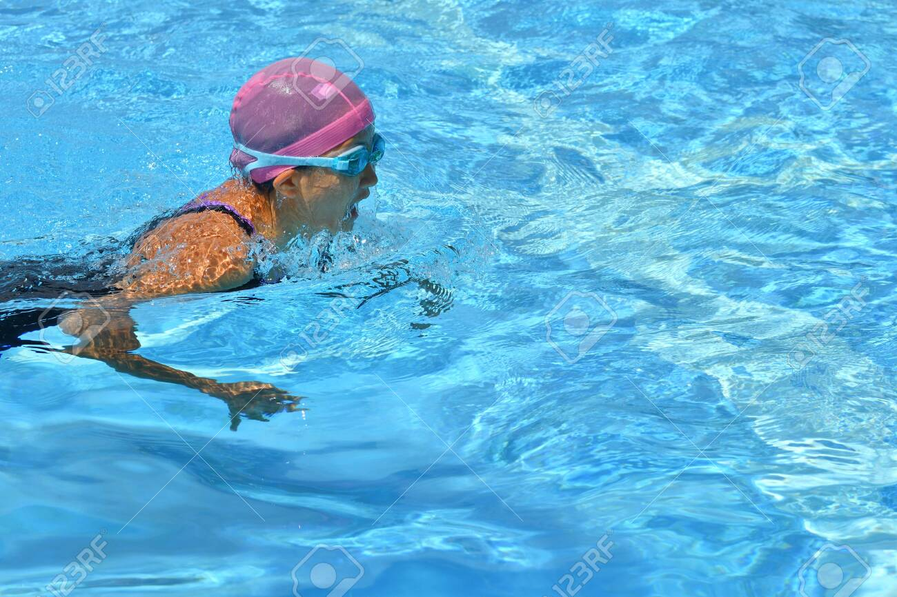 Japanese girl is swimming the stroke in the pool - 130422902