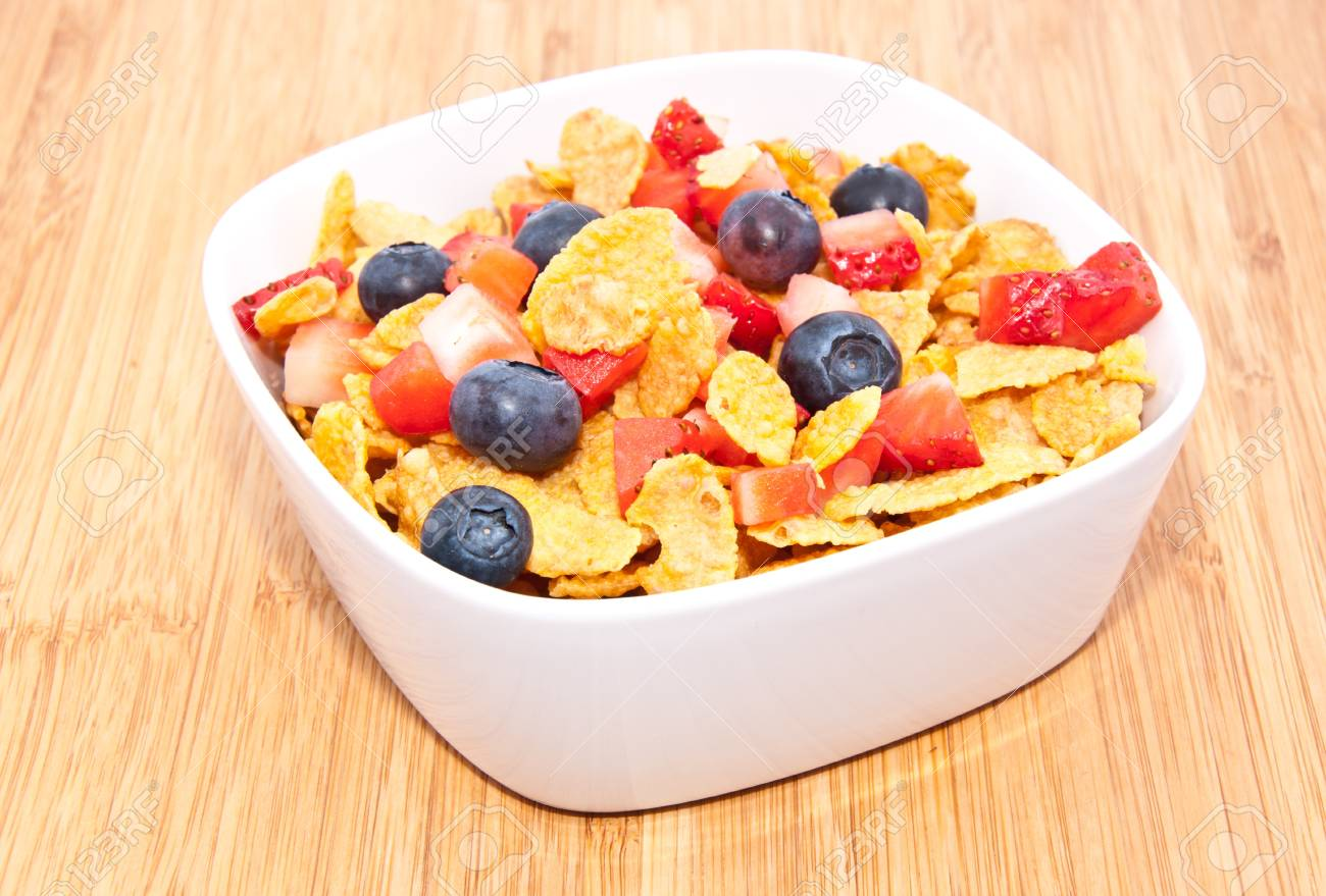 Heap of Cornflakes with fruits (Strawberries and Blueberries) in a bowl Stock Photo - 13699424